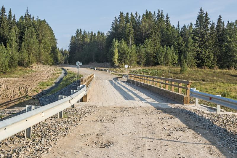 Puente concreto con la cubierta de madera puesta a través del río llevado, en su región infinita de Arkhangelsk, Federación Rusa, fotografía de archivo libre de regalías