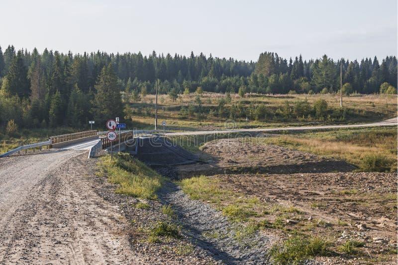 Puente concreto con la cubierta de madera puesta a través del río llevado, en su región infinita de Arkhangelsk, Federación Rusa, imagen de archivo libre de regalías