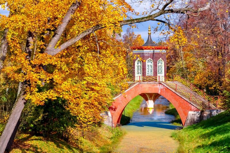 Puente cruzado en follaje del otoño en el parque de Alexander, Tsarskoe Selo Pushkin, St Petersburg, Rusia fotografía de archivo