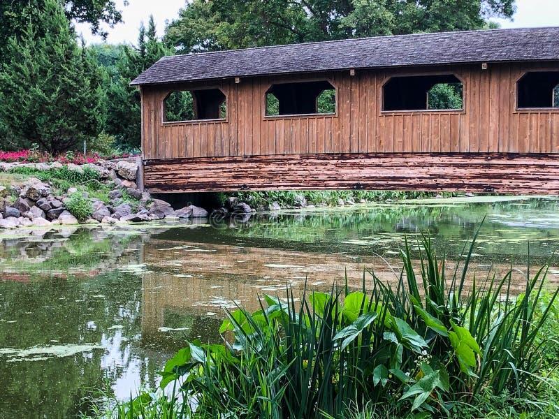Puente cubierto de madera de Brown sobre el agua en parque de la ciudad imagen de archivo libre de regalías