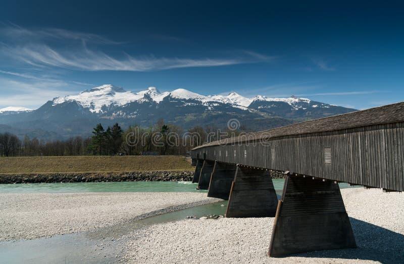 Puente cubierto de madera histórico a través del Rin con paisaje de la montaña y el cielo azul en el fondo fotos de archivo libres de regalías