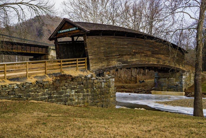 Puente cubierto jorobado sobre una corriente congelada - 2 foto de archivo