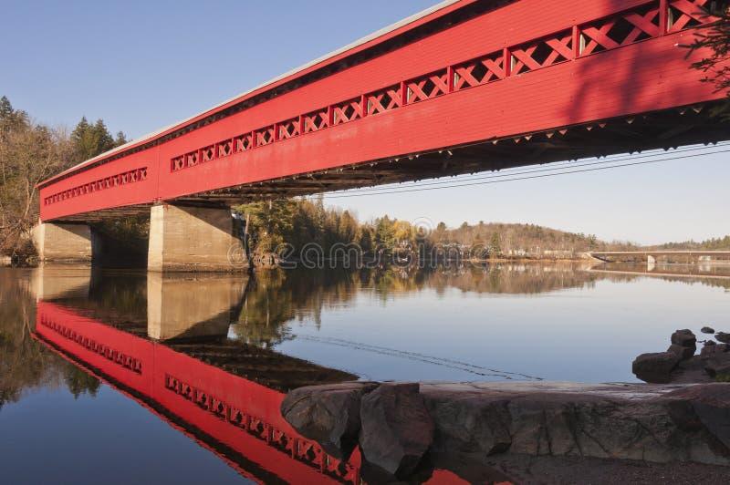 Puente cubierto rojo con la reflexión en agua imágenes de archivo libres de regalías