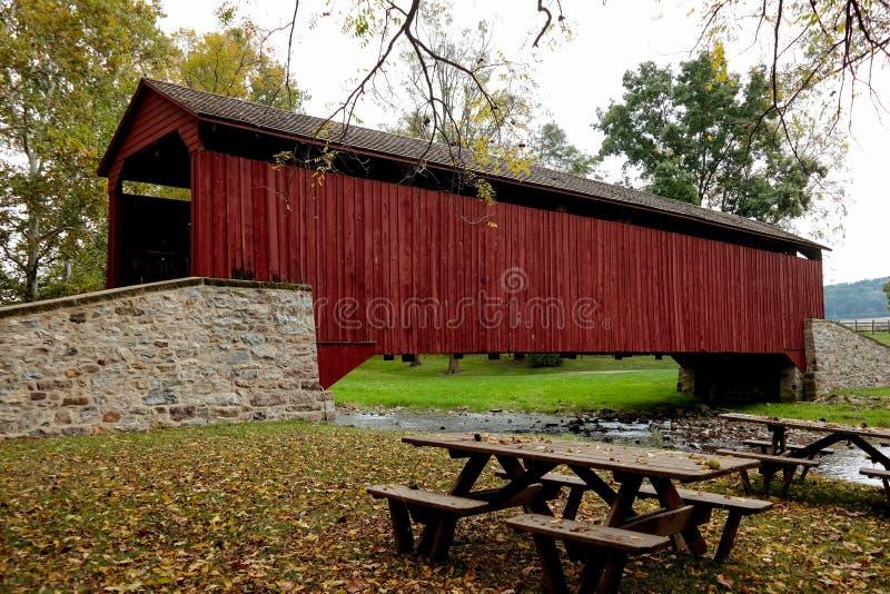 Puente cubierto y mesas de picnic de la fragua de la piscina foto de archivo