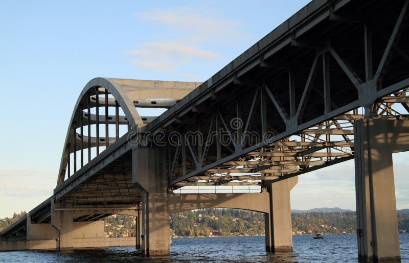 Puente de arco concreto y de acero sobre el agua imagenes de archivo