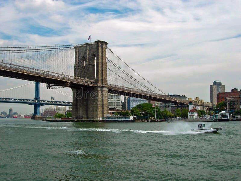 Puente de Brooklyn en East River con el barco de policía de la patrulla del puerto fotografía de archivo