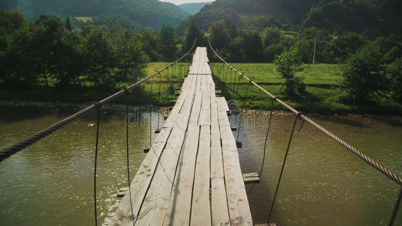 Puente de cuerda de la tensión con decking de madera sobre la corriente de la montaña imagenes de archivo