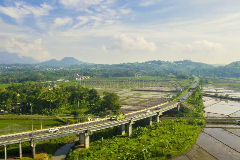Puente de la manera del peaje de Transporte-Java con tierras de labrantío imagen de archivo libre de regalías