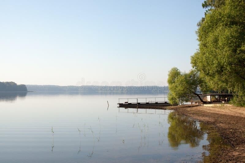 Puente de la pesca en la orilla de un lago del bosque en la madrugada en la niebla fotos de archivo libres de regalías