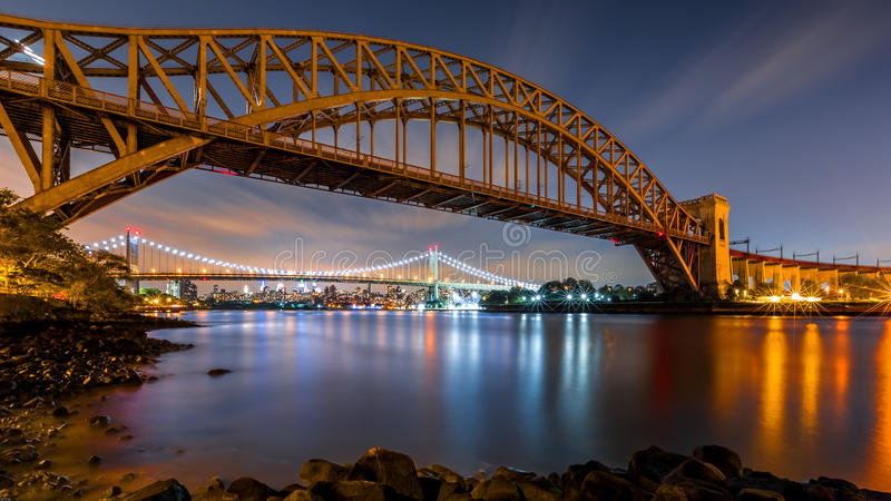 Puente de la puerta y de Triboro del infierno por noche imagen de archivo
