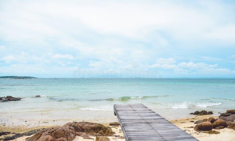 Puente de madera en la playa y el cielo de las rocas, nublado y azul, fondo del verano imagenes de archivo