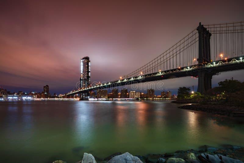 Puente de Manhattan del horizonte de New York City en la oscuridad imagen de archivo