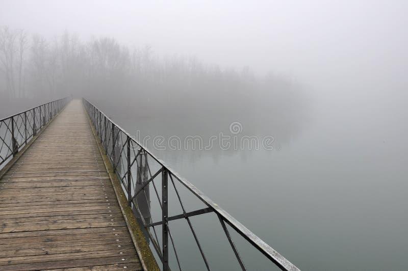 Puente de Pedestiran en la niebla, río del adda fotografía de archivo