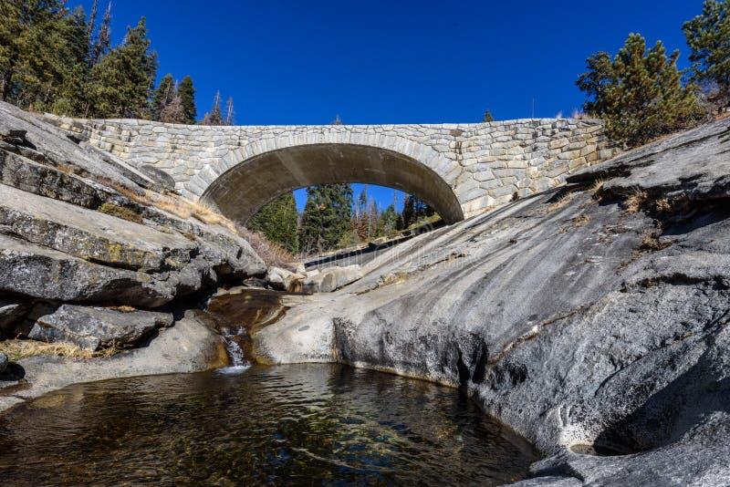 Puente de piedra sobre un río en las montañas foto de archivo libre de regalías
