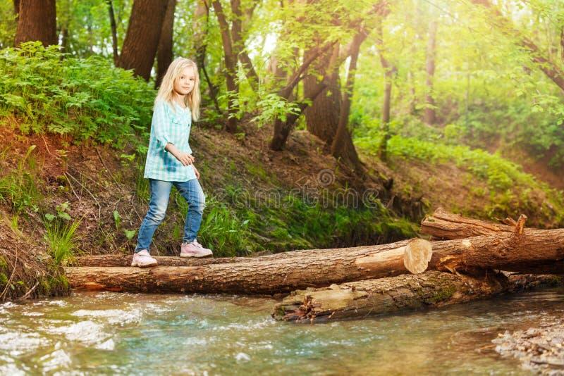 Puente de registro de la travesía de la niña en el bosque fotos de archivo