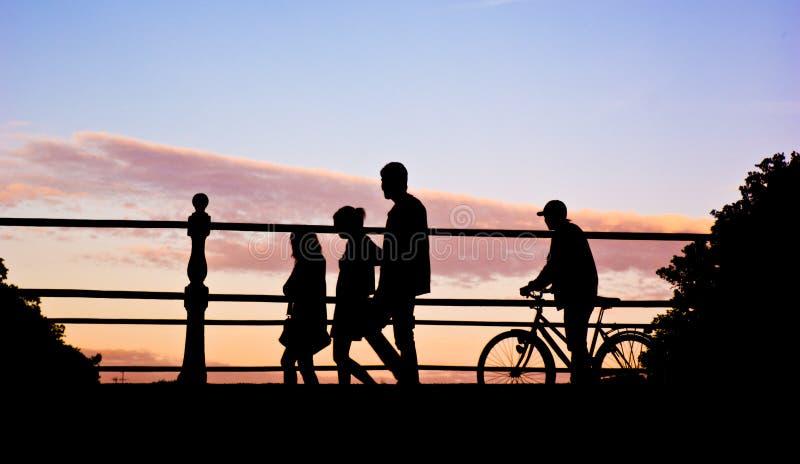 Puente de travesía de la gente en puesta del sol foto de archivo libre de regalías