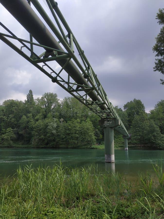 Puente del gas sobre el río en cielo nublado y tempestuoso foto de archivo libre de regalías