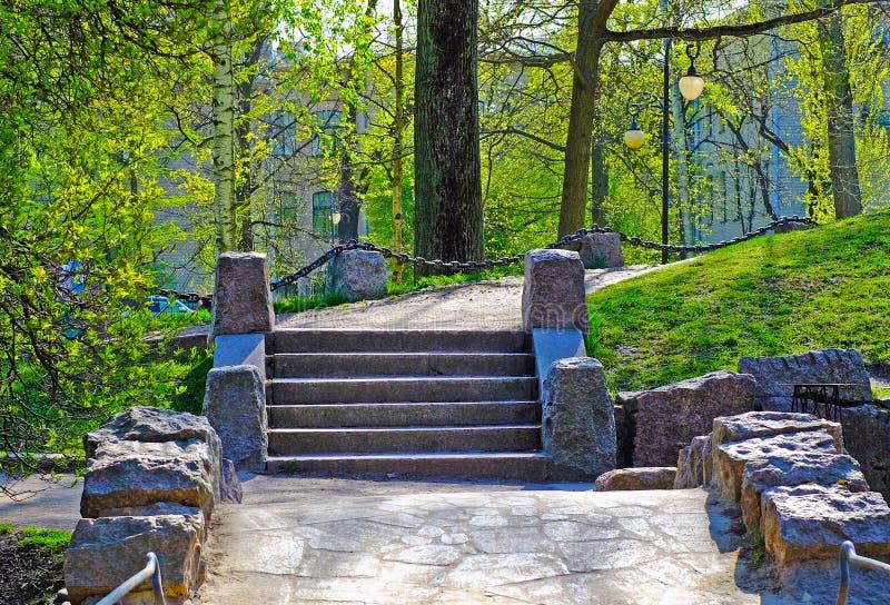 Puente del granito en el parque de St Petersburg El tiempo caliente de la primavera imagen de archivo