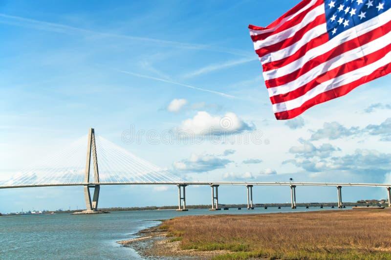 Puente del Jr El puente en Charleston, Carolina del Sur, con la estrella spangled la bandera en el primero plano imagenes de archivo