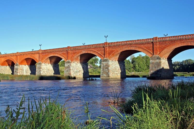 Puente del ladrillo a través del río Venta en Kuldiga, Letonia foto de archivo