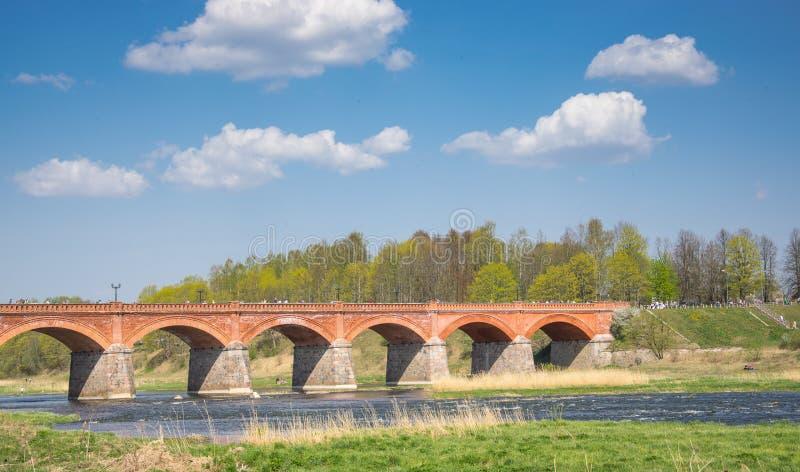 Puente del ladrillo a través del río de Venta en la ciudad de Kuldiga en Letonia fotos de archivo