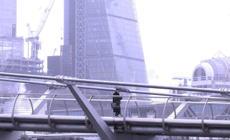 Puente del milenio, Londres Reino Unido 20 de enero de 2018 Una señora con el paraguas que manda un SMS como ella camina solament foto de archivo libre de regalías