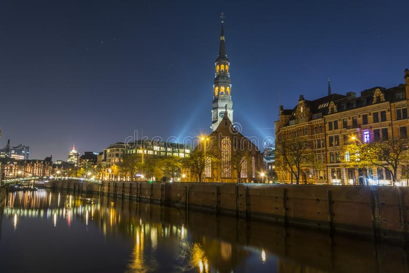 Puente en Speicherstadt en luz y cielo de la noche de Hamburgo Opinión de la iglesia imagenes de archivo