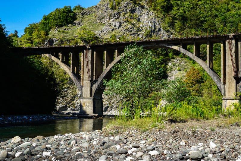 Puente ferroviario abandonado del arco a través del río acueducto Tkurchal Tkvarchelli Abjasia del este foto de archivo