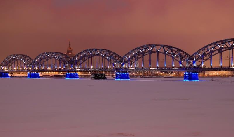 Puente ferroviario de Riga en la noche fotos de archivo
