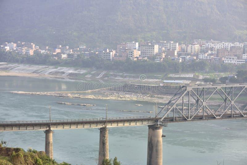Puente ferroviario a través del río Yangzi y de la pequeña ciudad del paisaje imagen de archivo libre de regalías