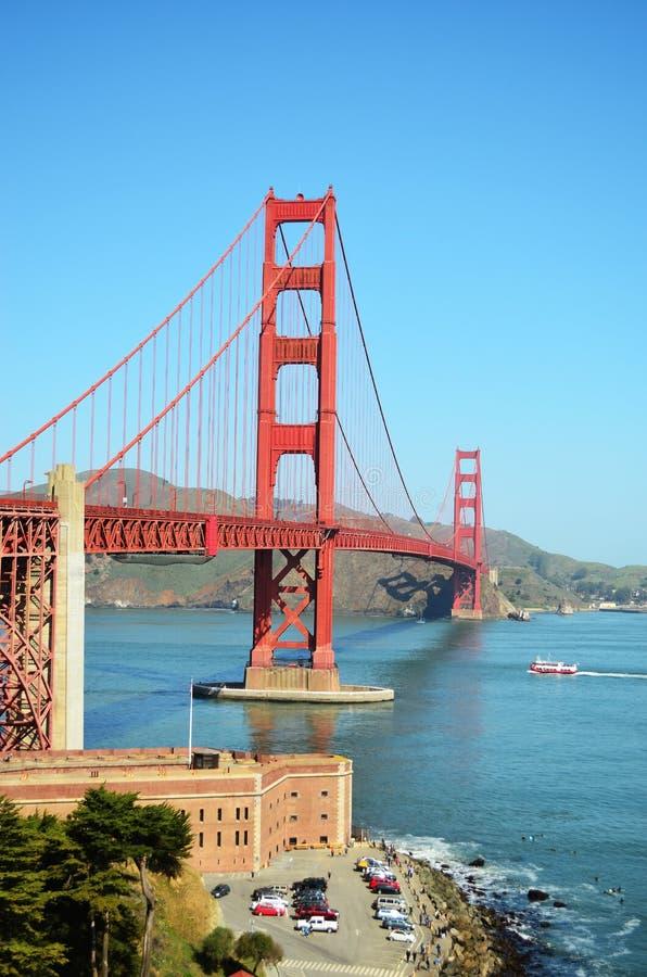 Puente Golden Gate con un fuerte y personas que practica surf en el primero plano fotografía de archivo