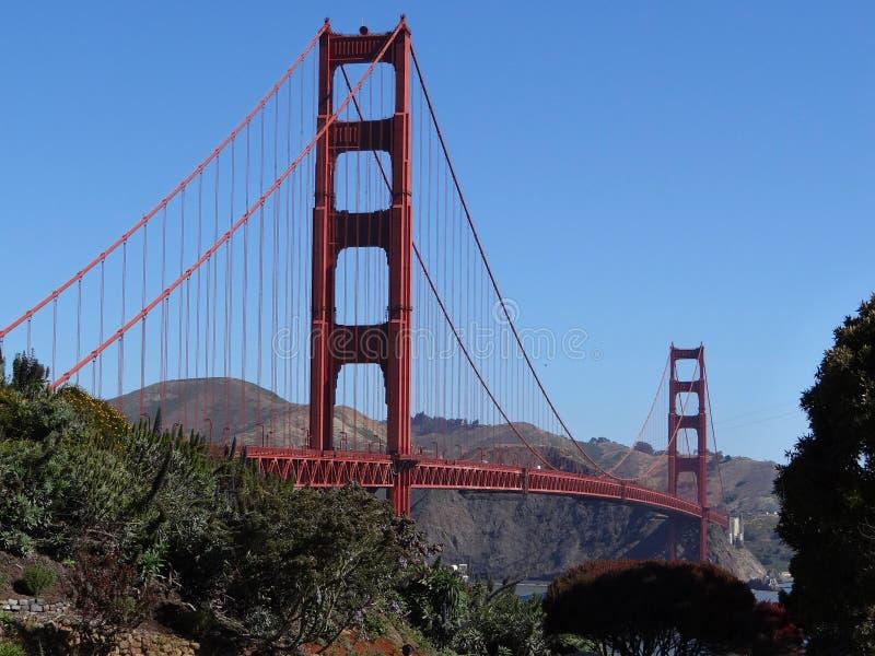 Puente Golden Gate en San Francisco, California con los árboles que enmarcan, el cielo azul y las montañas fotos de archivo