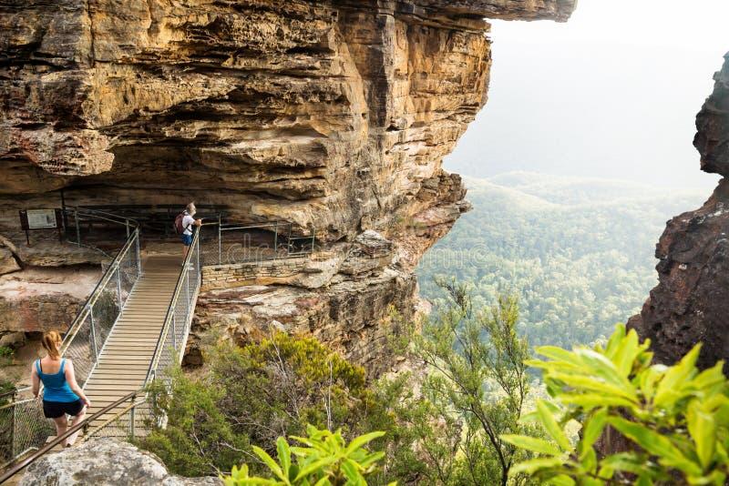 Puente a las hermanas de la formación de roca tres con los caminantes que miran en el valle, Katoomba, Nuevo Gales del Sur, Austr imagenes de archivo