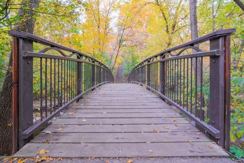 Puente peatonal sobre cala en Minneapolis - en caída con colores del otoño en hojas del árbol - amarillos y verdes foto de archivo libre de regalías