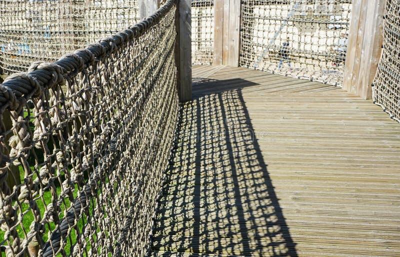 Puente que camina de madera con la cerca de la cuerda imagen de archivo libre de regalías