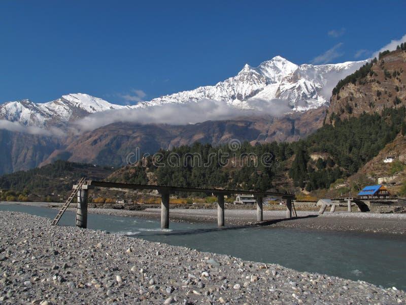 Puente, río y Dhaulagiri dañados, un mustango más bajo Nepal de Marsyangdi imagenes de archivo