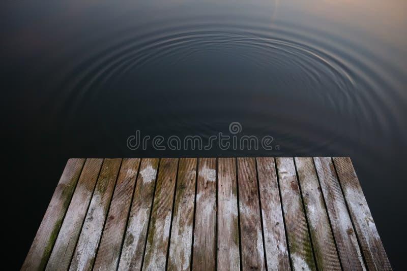 Puente rústico viejo del embarcadero del grunge en los wi del negro oscuro de un lago del agua azul imagenes de archivo