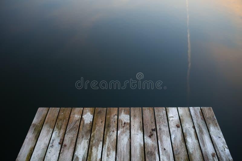 Puente rústico viejo del embarcadero del grunge en los wi del negro oscuro de un lago del agua azul imagen de archivo