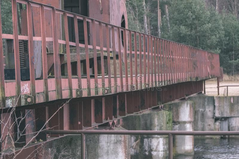 puente rojo viejo del metal sobre el agua - mirada retra del vintage imagenes de archivo