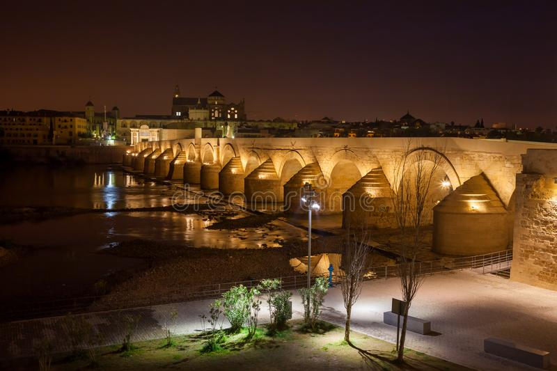 Puente Romano in Cordoba at Night. Spain, Cordoba, Roman Bridge Puente Romano on Guadalquivir River and Mosque Cathedral at night royalty free stock photo