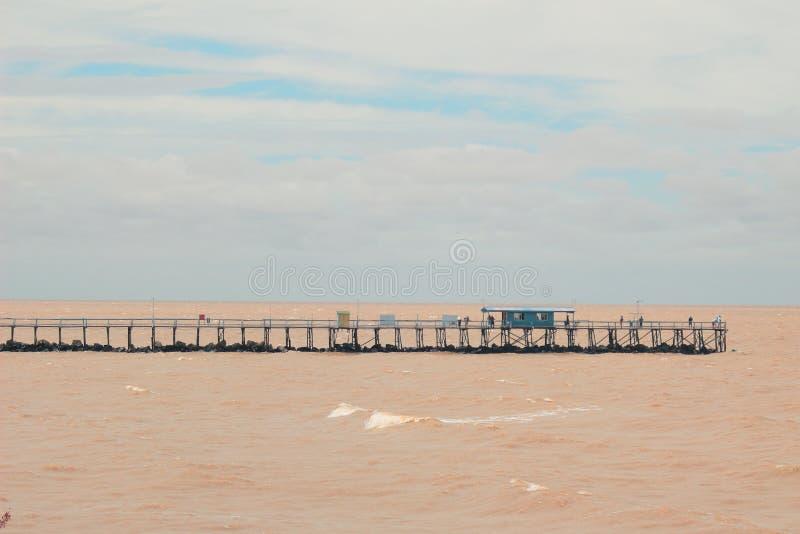Puente sobre el Brown RÃo de La Plata en la Argentina, Buenos Aires con una pequeña casa azul y un cielo azul imagenes de archivo