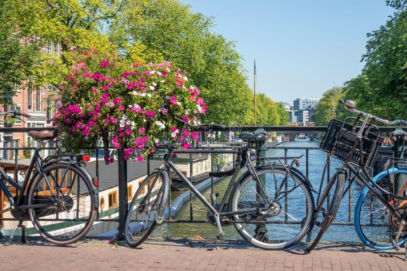 Puente sobre el canal con las bicicletas y las flores, Amsterdam, el Nethelands fotos de archivo