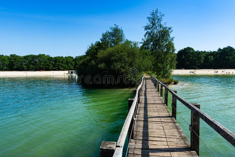 Puente sobre el lago con una playa en el fondo imagenes de archivo