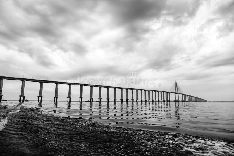 Puente sobre el mar en Manaus, el Brasil Paso del camino sobre el agua en el cielo nublado Arquitectura y diseño Destinación del  fotos de archivo