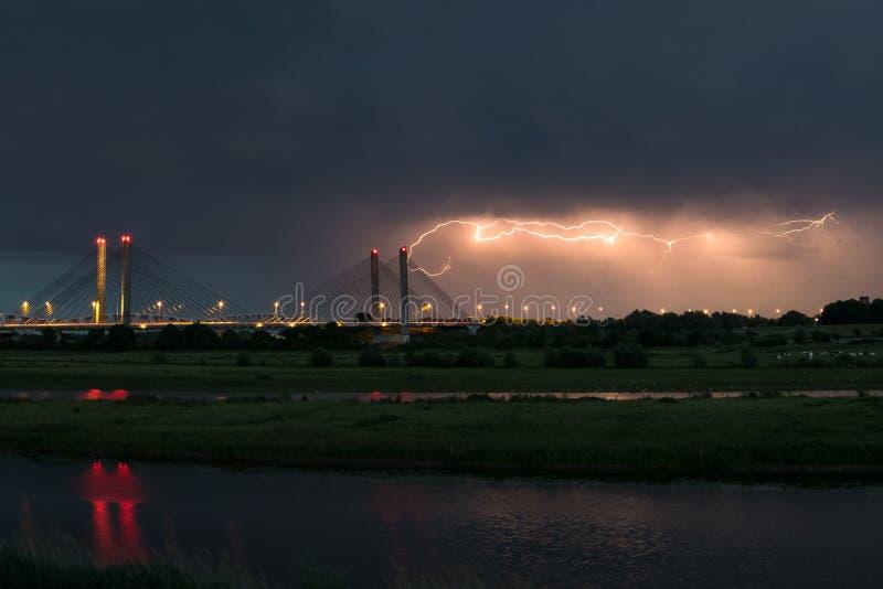 Puente sobre el río 'Waal 'en los Países Bajos mientras que un rayo horizontal viaja a través del cielo fotografía de archivo libre de regalías