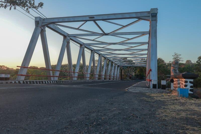 Puente sobre el río con la estructura del hierro Puente de acero en la isla de Bali Caminos y la mayoría a través de la cama de r fotografía de archivo libre de regalías