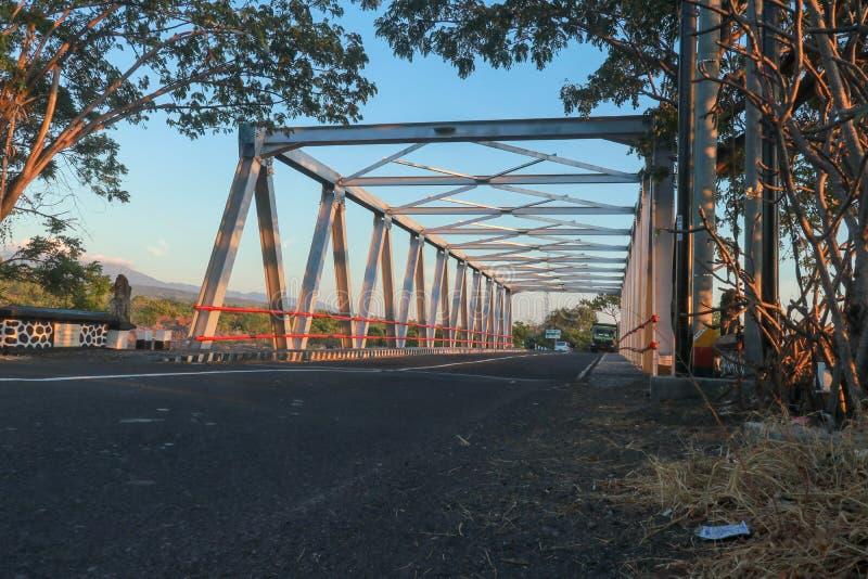 Puente sobre el río con la estructura del hierro Puente de acero en la isla de Bali Caminos y la mayoría a través de la cama de r foto de archivo