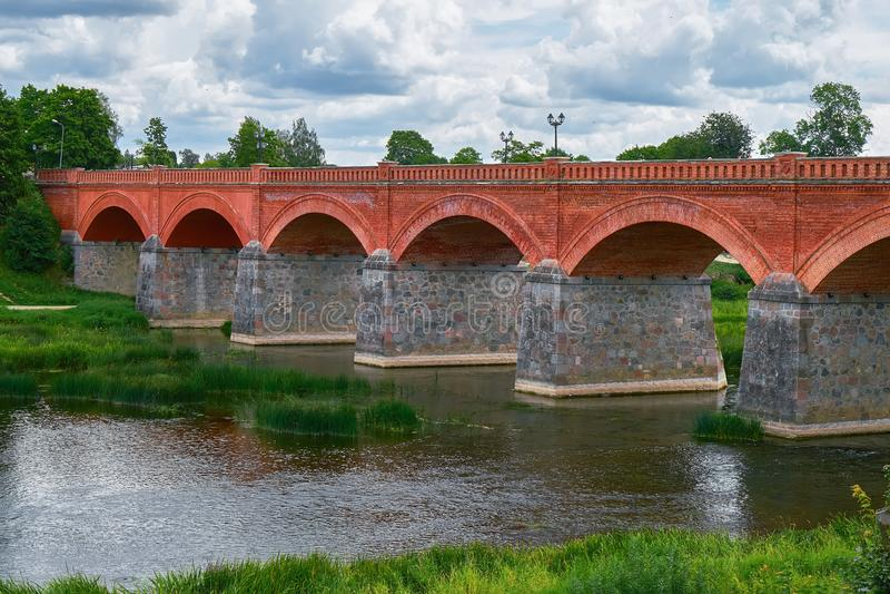 Puente viejo del ladrillo a través del río Venta en la ciudad de Kuldiga, foto de archivo libre de regalías