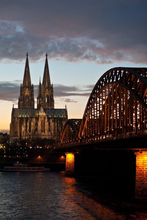 Puente y Dom Cathedral de Colonia en la puesta del sol imagen de archivo