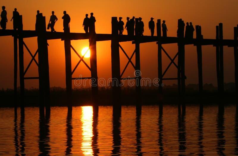 Puente y gente de U Bein en la puesta del sol foto de archivo